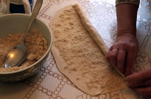 From one of the long sides, start slowly rolling the dough across