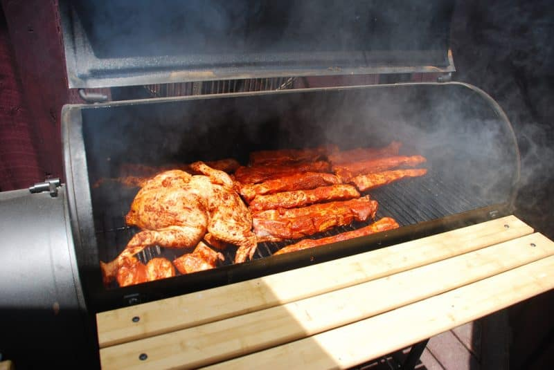 Offset smoker smoking chicken and pork ribs