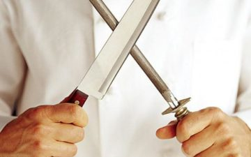 A chef is pictured holding a knife and a honing rod