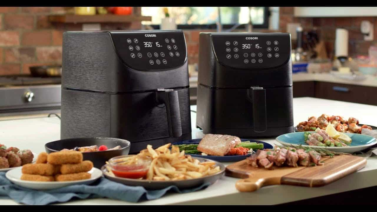 Two air fryers on a countertop with air-fried food in front