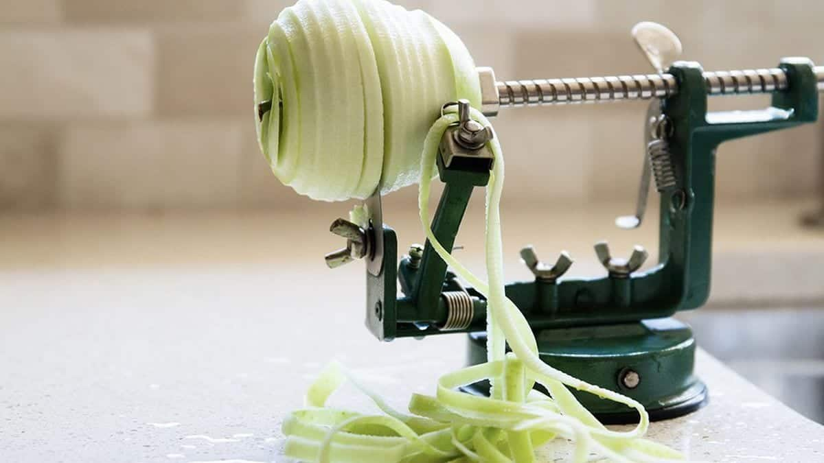 Peeling an apple using an apple peeler on a counter