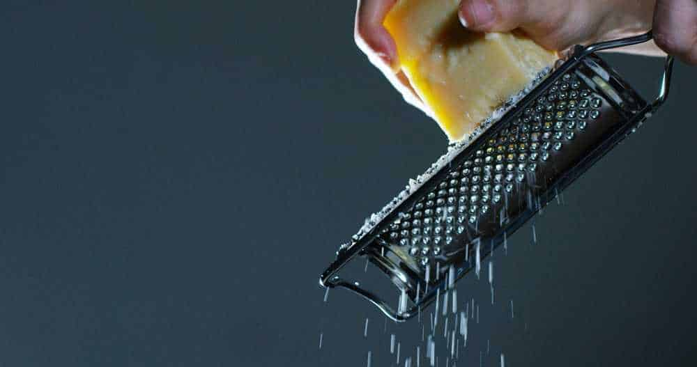 Using a lemon zester to grate cheese