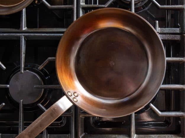 Seasoning carbon steel pan on stovetop