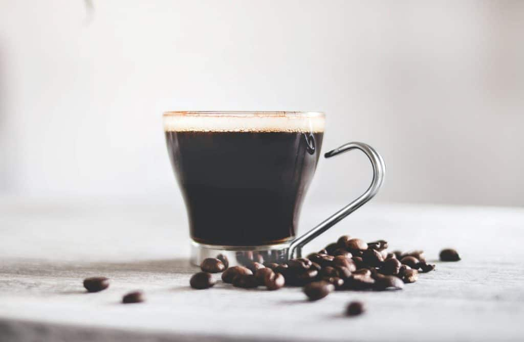 Cup of coffee and dark roast coffee beans