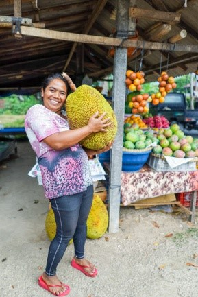Woman holding a large jackfruit