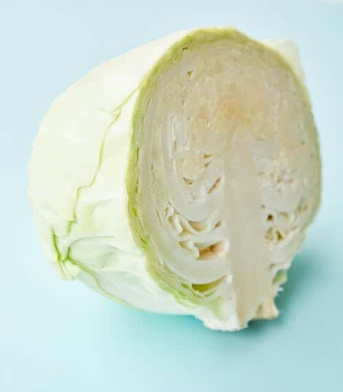 a head of cabbage halved and ready to cut.