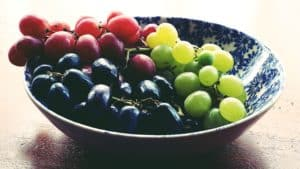 green red and black grapes in a bowl.